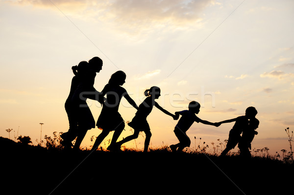1218731_stock-photo-silhouette-group-of-happy-children-playing-on-meadow-sunset-summertime